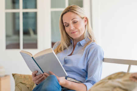 Happy mature woman reading storybook on couch. Charming woman reading a novel sitting on a sofa in living room. Woman reading a book and smiling at the porch.