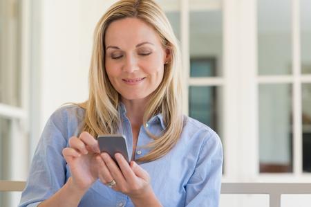 携帯電話を用いた金髪熟女の肖像画。笑顔幸せな女がスマート フォンでメールをチェックします。幸せな女のテキスト メッセージの電話メッセージ