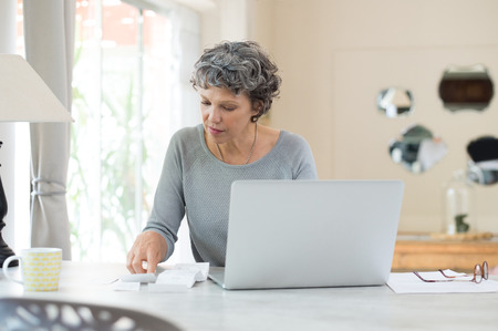 home expenses: Senior woman working on home finance. Mature woman checking bills at home. Older woman checking pension approval certificate with laptop at home. Stock Photo
