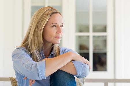 Frau sitzt vor dem Haus und zum Nachdenken über ihre neue Idee. Nachdenkliche Mitte Frau im Urlaub zu Hause entspannen. Portrait von reifen Frau, die ihre Zukunft zu planen.