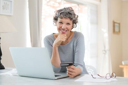 행복 한 수석 여자 노트북을 사용 하여 지폐의 온라인 지불 만들기. 신용 카드로 온라인 쇼핑 웃는 성숙한 여자. 인터넷 뱅킹 및 카메라를 찾고 신용 카 스톡 콘텐츠