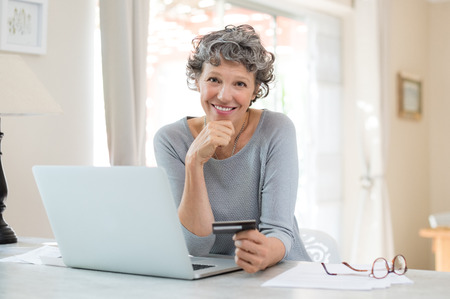 Happy senior woman making online payments of bill using laptop. Smiling mature woman shopping online with credit card. Pensioner holding credit card for internet banking and looking at camera. Banque d'images