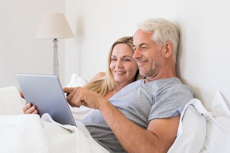 年配のカップルは、自宅のベッドで横たわっている間デジタル タブレットを使用します。幸せな先輩カップルの寝室でタブレットでネット サーフィ