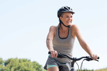 bycicle: Mature woman riding on mountain bike in the park. Portrait of a happy senior woman riding bicycle in a park. Athletic woman wih helmet cycling and looking away.