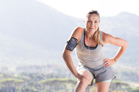 escucha activa: corredora mayor descanso después de correr en un parque. mujer madura orgullosos extiende en el parque y mirando a la cámara. Mujer mayor activo de completar su diaria rutina de ejercicios.