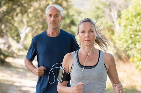 年配の男性と女性が公園で音楽を聴きながらのジョギングします。熟女のカップルは、一緒に公園で実行しています。男を引退し、半ば女性運動屋 写真素材