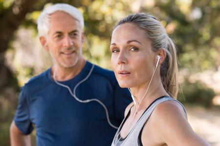 deporte: Senior pareja descansando después de una larga carrera en el parque. Cansado mujer madura de escuchar música mientras se relaja después de hacer footing. Mujer mayor que mira a la cámara después de entrenar al aire libre.