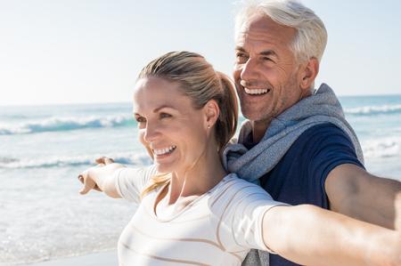 행복한 수석 몇 팔을 뻗은 해변에 서 멀리보고. 밝고 화창한 날에 해변에서 행복 한 커플. 은퇴 한 남편과 자신의 미래에 대해 생각 미소 아내.