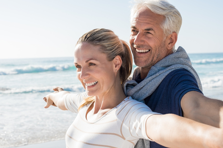 free thinking: Happy senior couple standing on beach with arms outstretched and looking away. Happy couple at beach on a bright sunny day. Retired husband and smiling wife thinking about their future.