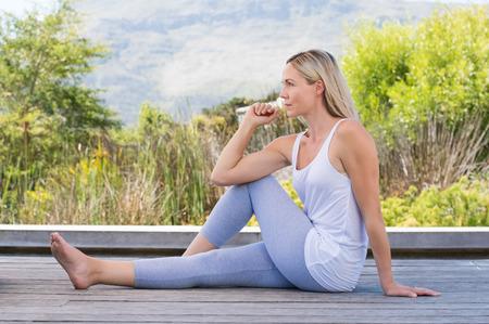 Mujer mayor sonriente de estiramiento y ejercicio al aire libre. De alto relajado mujer haciendo yoga se extiende después del ejercicio. Hermosa mujer de relax con el yoga plantean.