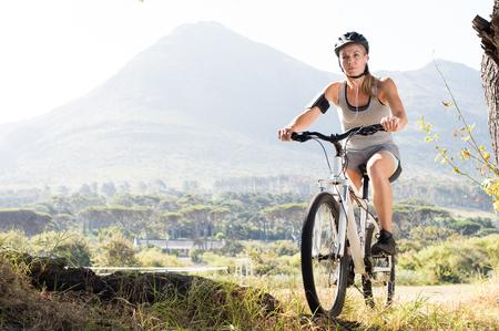 escucha activa: Retrato de bicicleta de monta�a mujer mayor en el campo. Mujer activa ciclo maduro del montar a caballo en la naturaleza mientras se escucha m�sica con reproductor de mp3. Mujer deportiva sana de montar su bicicleta en el parque.