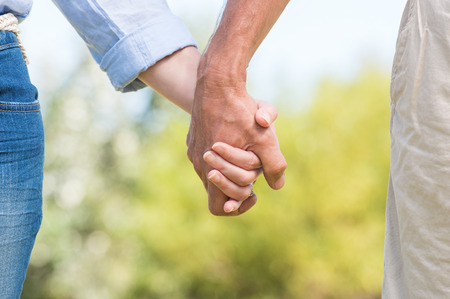 senior women: Closeup of couple holding hands outdoor. Romantic mature couple walking and holding hands. Close up hands of senior couple.