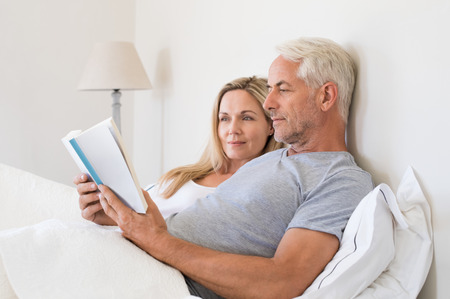 Senior couple reading a book in bed before going to sleep. Relaxed senior man and smiling woman reading together a book lying on bed. Retired man reading a book to his wife in their home. Stock Photo