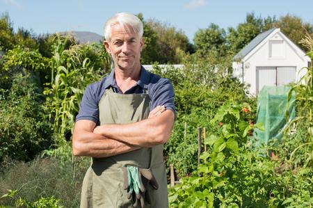 Erfolgreiche reifen Mann im Feld. Portrait eines älteren Mannes in die Kamera im Gemüsegarten suchen. Glückliche Gärtner zufrieden und lächelnd.