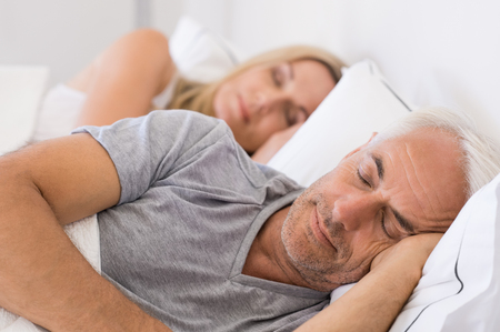 durmiendo: hombre mayor y una mujer dormida. hombre mayor y una mujer descansando con los ojos cerrados. pareja madura durmiendo juntos en la cama.