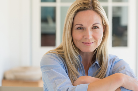 Happy mature woman relaxing on her couch at home in the living room. Close up face of senior woman looking at camera. Portrait of happy woman in blue shirt smiling. Stockfoto