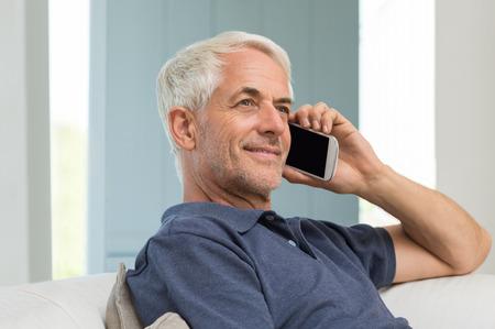 家で携帯電話を使用して陽気な年配の男性。自宅のソファに座って携帯電話で話しているシニアの幸せな男の肖像画。引退した笑みを浮かべて男が