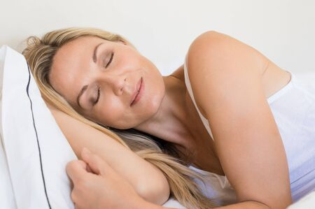 mature woman: Portrait of a senior woman sleeping with head on a white pillow. Beautiful senior woman resting with closed eyes in her bed. Close up face of mature woman resting in bed.
