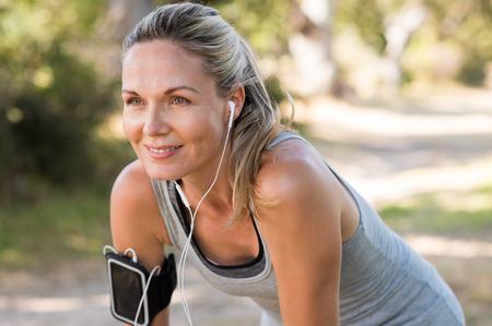 motion: Porträtt av atletisk mogen kvinna som vilar efter jogging. Vacker senior blond kvinna som kör på parken på en solig dag. Kvinnlig löpare lyssnar på musik medan du joggar.