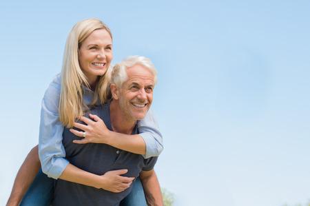 年配の男性は、青い空を背景に幸せな女性におんぶを与えます。 年配の男性におんぶに笑みを浮かべて熟女。引退したカップルの楽しいと考える。