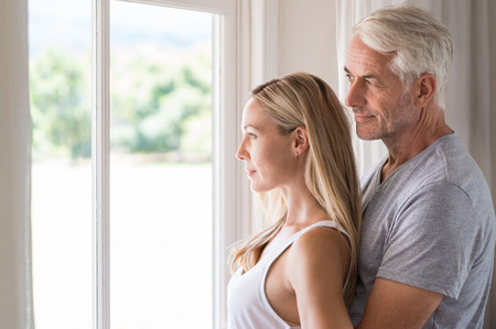 young wife: Serene mature couple looking outside the window. Senior couple thinking the future in the morning time. Happy smiling man embracing from behind his young wife and thinking about the retitrement.