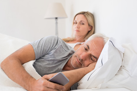 adultery: Jealous woman spying her husband mobile phone while he is reading a message. Senior couple in bed while wife is angry as husband using smartphone. Senior husband ignoring wife and texting on smartphone. Stock Photo