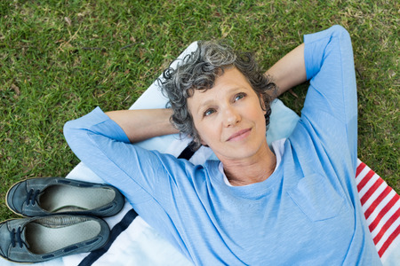 Pensive senior woman lying on towel on grass. High angle view of thoughtful mature woman thinking. Retired woman contemplating her life after retirement. Stock Photo