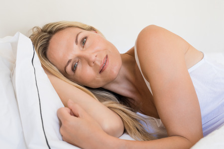 awake: Beautiful happy smiling blond woman waking up on bed. Portrait face of mature woman relaxing on bed and looking at camera. Beautiful senior woman with her head resting on the white pillow.