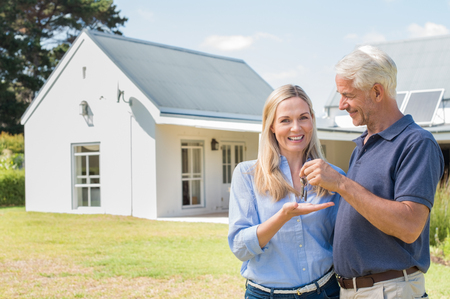 home loan: Cheerful senior couple standing outside their new house with keys. Retired man giving new house keys to his wife. Senior man and mature woman in the garden of their new house. Stock Photo
