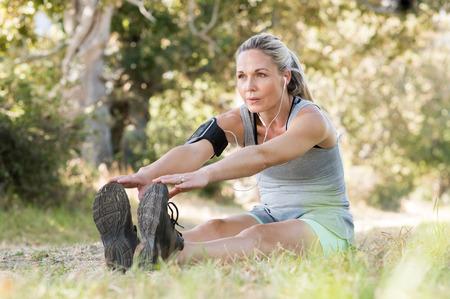 年配の女性は音楽を聴きながら公園で運動。屋外の彼女のストレッチをしている年配の女性。良いトレーニング セッション後のストレッチ運動の熟
