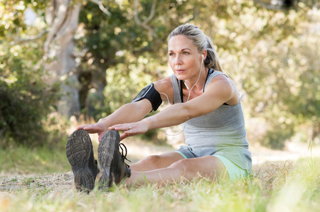 mature women: Senior woman exercising in park while listening to music. Senior woman doing her stretches outdoor. Athletic mature woman stretching after a good workout session.