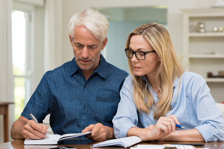 financials: Mature couple calculating bills at home. Mature woman wearing spectacles discussing home economics. Senior man worried about financials at home while woman looking the bills.