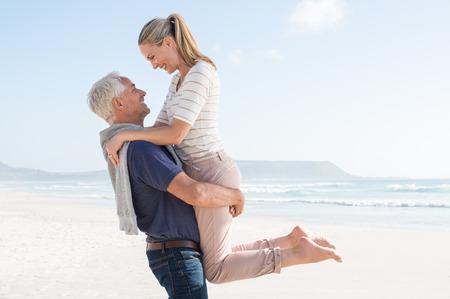 Leuk hoger paar knuffelen op het strand op een zonnige dag. Gelukkig stel met plezier samen op het strand. Senior man carrrying haar vrouw op het strand en kijken naar elkaar. Stockfoto