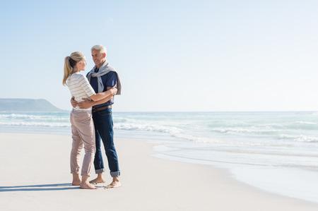 陽気な大人のカップルは、コピーの右上の領域で、ビーチで採用します。幸せな先輩カップルが海辺でお互いを見てします。ロマンチックな海で夏