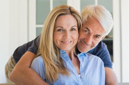 parejas enamoradas: Retrato de una pareja sonriente alto mirando a la cámara. Hombre mayor abrazando a su esposa. Sonrisa feliz pareja se retiró en el amor.