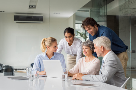 group strategy: Business people having meeting around table in modern office. Group of businessmen and businesswomen working together on computer during a meeting. Senior businesswoman showing marketing strategy to her team on laptop.