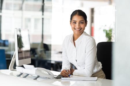 コンピューターとノートを取る前に彼女の机に座って美しい若い実業家の肖像画。多民族受付カメラ目線します。笑顔の多民族のビジネス女性のオ