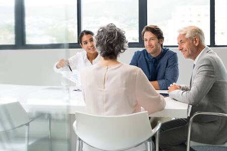 happy workers: Positive multiethnic business people holding a meeting to sum up the results of the year. Group of happy business team during a meeting in a modern board room. Young businesswoman showing a business graph of the company to senior leader.