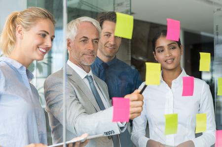 プロフェッショナルなビジネス チーム付箋上のアイデアを議論します。ビジネスマンは、付箋紙に書かれた作品を示します。粘着ノートで議論する