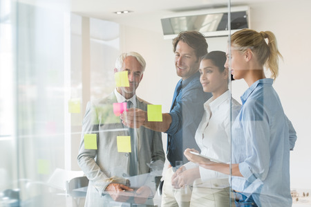 sticky: Smiling businessmen and businesswomen looking at sticky notes in board room. Creative business team looking at adhesive notes in office. Successful business teamwork discussing over sticky notes.