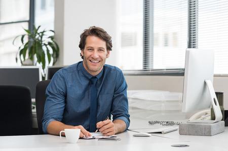 オフィスのデスクで働く陽気な青年実業家。成功するビジネス人が一杯のコーヒーが付いているオフィスに座っています。幸せな青年実業家笑って