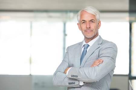 smiling businessman: Portrait of a senior businessman with arms crossed in his modern office. Successful business man with arms folded looking at the camera. Portrait of a happy senior businessman in formal smiling.