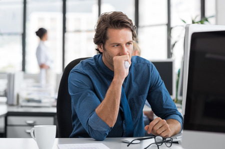 Tired and depressed businessman sitting in office at the table. Tensed businessman with hand on mouth staring at computer screen. Stressed business man thinking about solution while looking at computer.