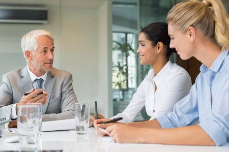 manager team: Senior manager giving training to new businesswomen in office. Group of businesspeople working together during a meeting in boardroom. Human resources director talking with new employees. Stock Photo