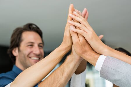 high: Group of multiethnic businesspeople giving high five. Close up of business hands giving high five in office. Happy business team high fiving in a modern office. Stock Photo