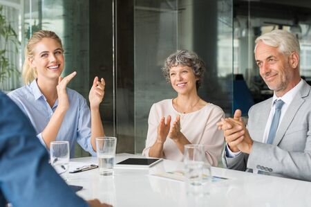Group of business people meeting in corporate conference room, applauding at a coworker during his presentation. Business group greeting employee with clapping and smiling. Businessmen and businesswomen applauding at seminar.
