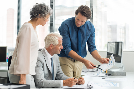 briefing: Business team meeting for financial report. Young employee briefing with senior leadership and businesswoman about new project. Business partners in a conversation over future growth. Stock Photo