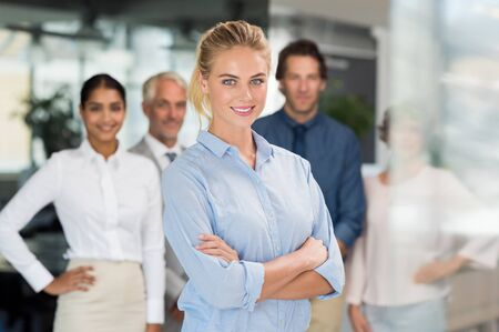 busineswoman: Portrait of a proud busineswoman looking at camera in a modern office. Successful happy woman standing with her staff in background. Beautiful young business woman smiling with colleagues in office.