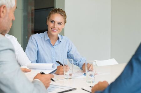 Young cheerful business woman making notes during a meeting. Businesswoman listening to senior businessman while in meeting. Happy young business woman in a brainstorming with colleague in office boardroom.