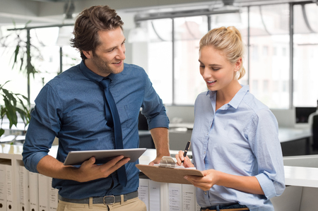 colleagues: Smiling businessman and young businesswoman talking in office. Manager and employee working together. Happy business man with digital tablet working with his assistant.